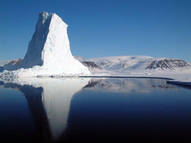 Eisberg vor großer Insel im Polarmeer
